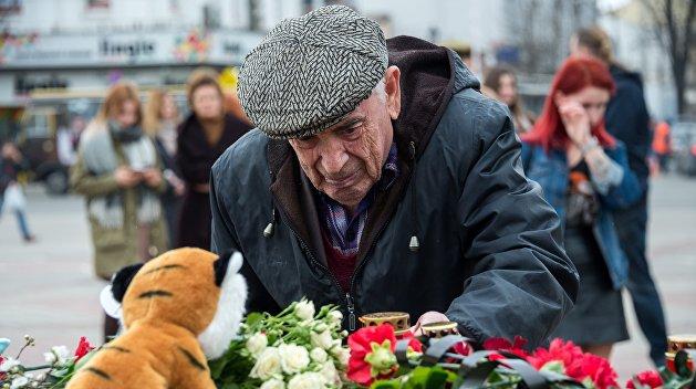 Жители ДНР несут цветы к стеле «Россия» в память о жертвах пожара в Кемерово